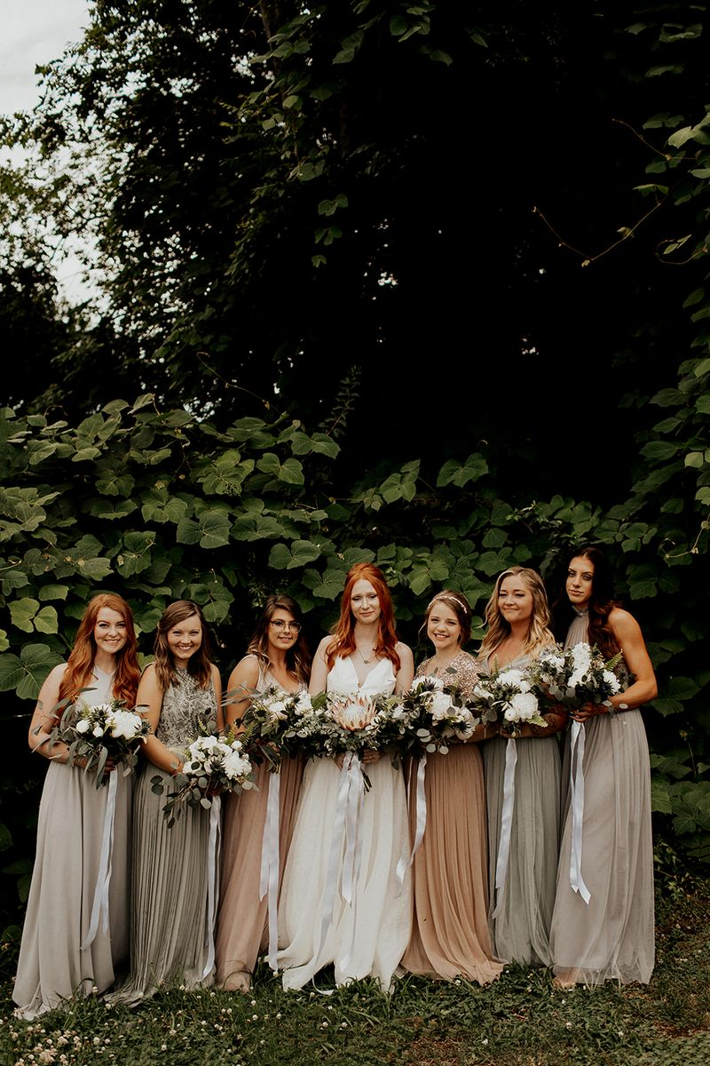 Bride and bridesmaids standing in line holding bouquets