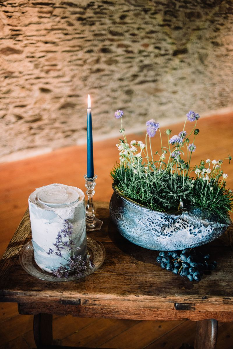 Simple wedding cake next to wildflowers in rustic pot