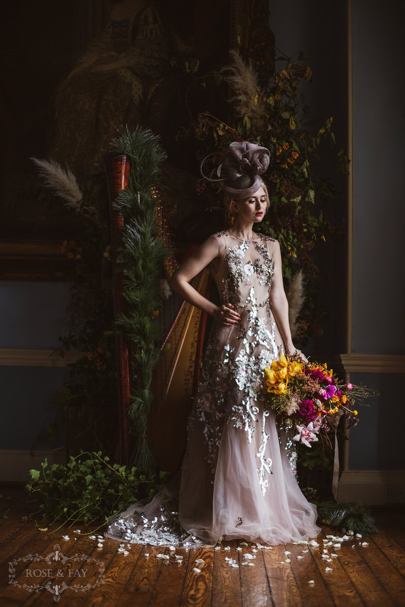 Bride wearing dress with silver detail and grey bridal hat