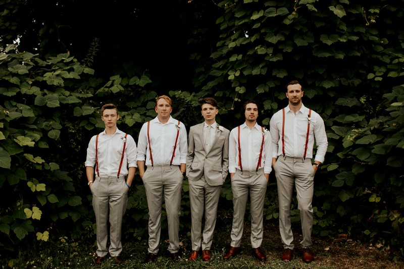 Groom standing with groomsmen wearing shirts and braces