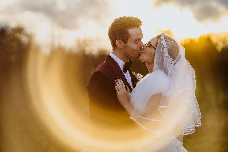 Bride and groom kissing framed in ring of light on camera lens - Picture by Lee Dann Photography