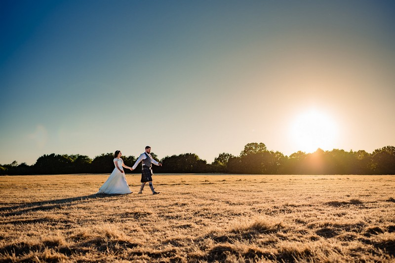 Bride and groom walking across field in hazy sunshine - Picture by Andy Dane Photography