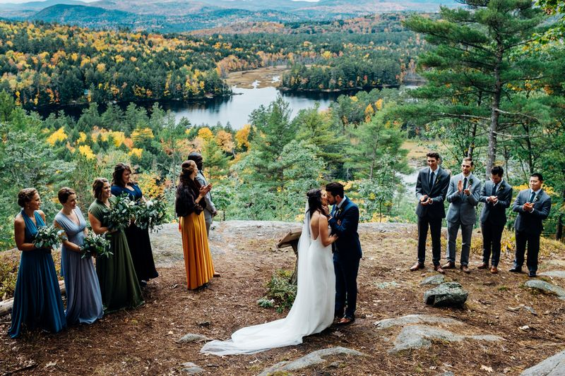 Outdoor wedding ceremony overlooking incredible view of trees, lakes and mountains - Picture by Marianne Chua Photography