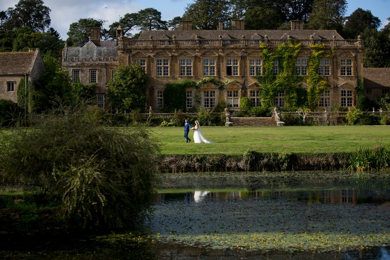 Bride and groom walking by lake in front of wedding venue - Picture by Martin Dabek Photography
