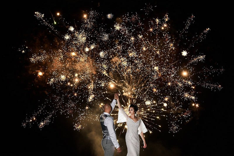 Bride and groom dancing in front of fireworks - Picture by Faye Amare Photography