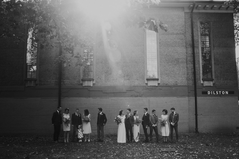 Old style black and white picture of wedding party standing in front of wall of building - Picture by Joasis Photography