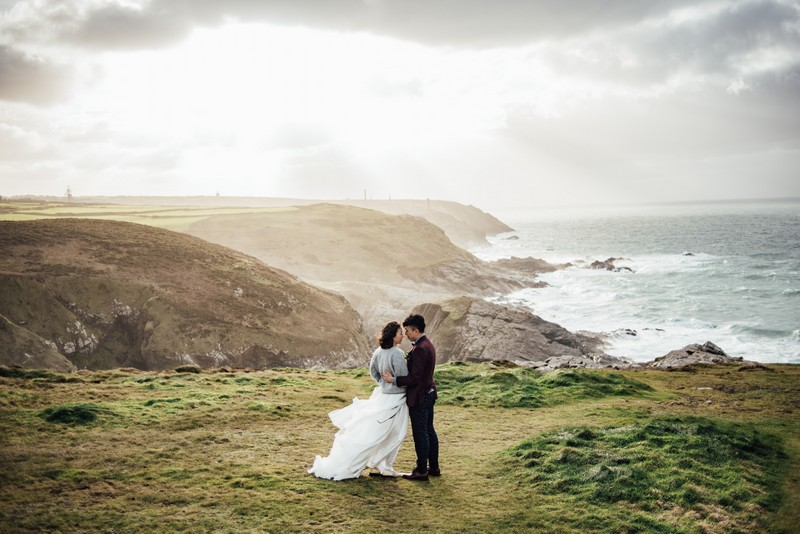 Bride and groom on top of cliff overlooking the sea - Picture by Liberty Pearl Photography