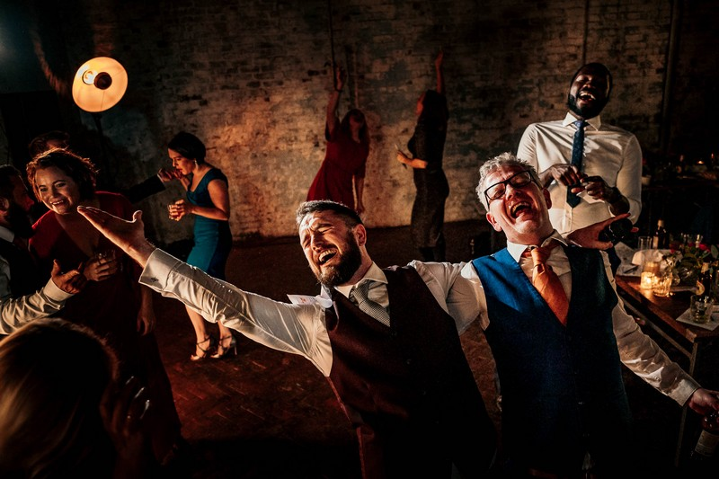 Two men singing enthusiastically at a wedding - Picture by Andrew Billington Photography