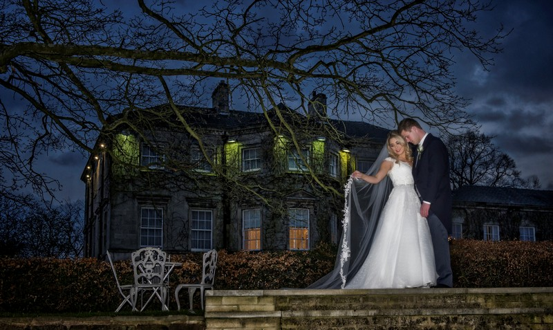 Bride and groom standing under tree in front of wedding venue at night - Picture by Image-i-Nation Photography