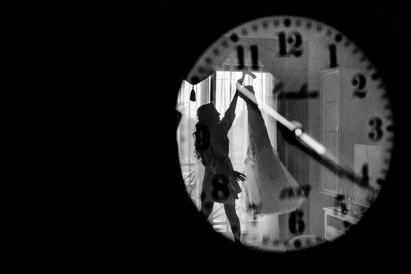 Reflection in clock of bride taking wedding dress down off rail - Picture by Sabina Mladin Photographer