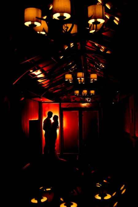 Silhouette of bride and groom at end of room lit with orange light from lamps - Picture by Matt Selby Photography