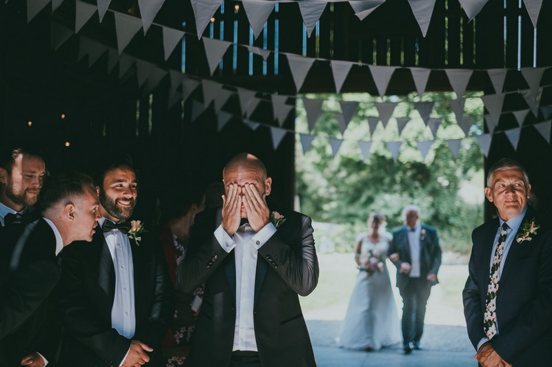 Groom with hands over his eyes to wipe away tears a sbride walks down the aisle - Picture by Ross Talling Photography
