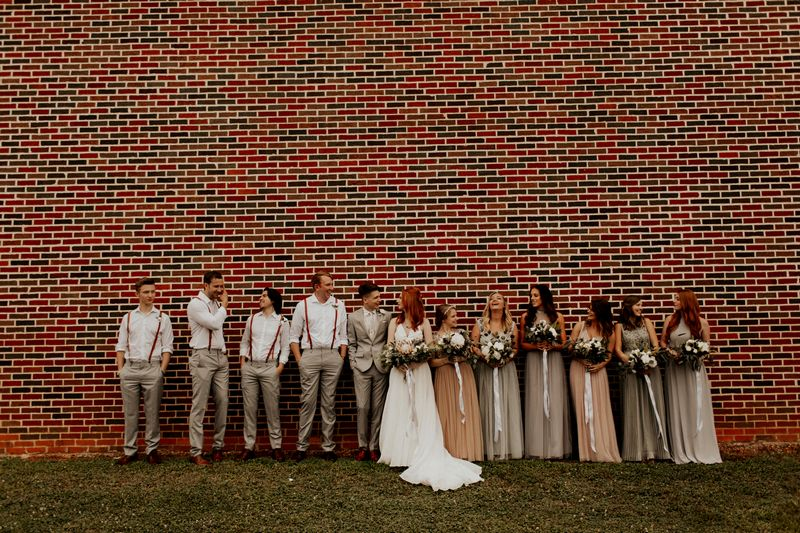 Bridal party standing in front of brick wall