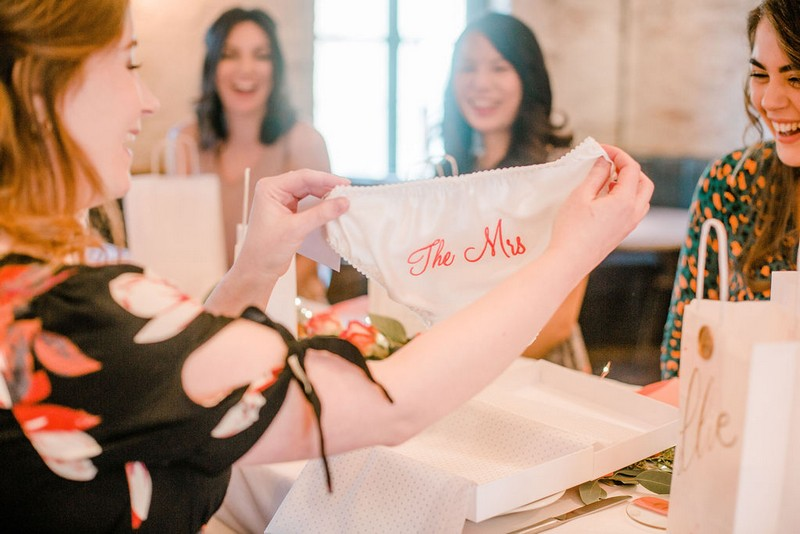 Bride-to-be holding bridal shower gift of knickers