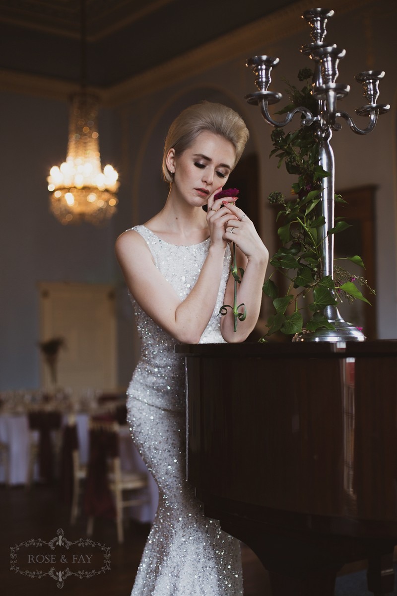 Bride standing holding rose next to piano