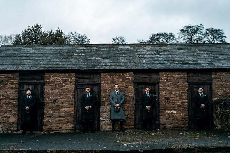 Groomsmen standing in front of doors of outbuilding
