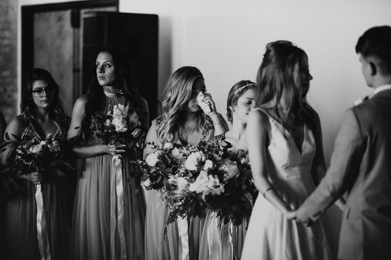 Bridesmaids wiping away tears during wedding ceremony