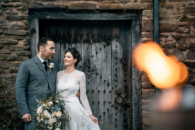 Bride and groom standing in front of door of outbuilding