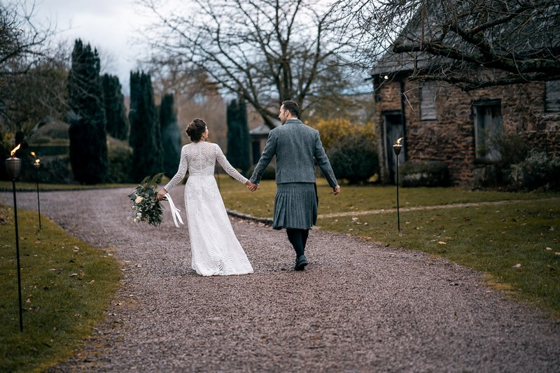 Bride and groom walking in grounds of Dewsall Court