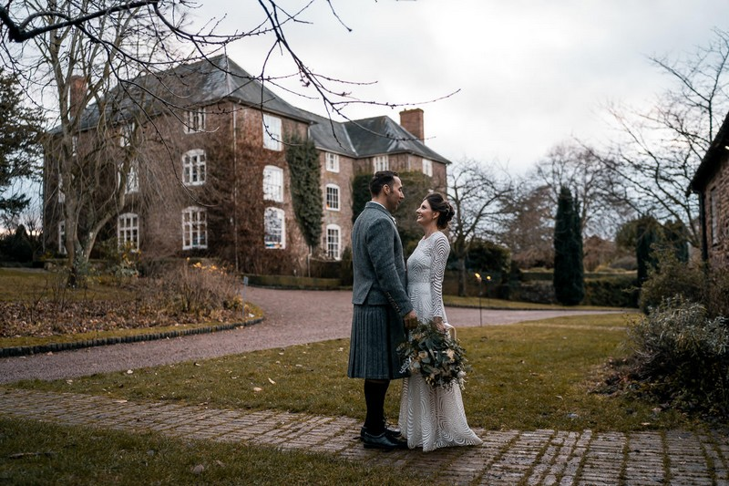 Bride and groom facing each other with Dewsall Court in background