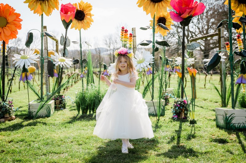 Flower girl walking though field of Giant Flowers from The Prop Factory