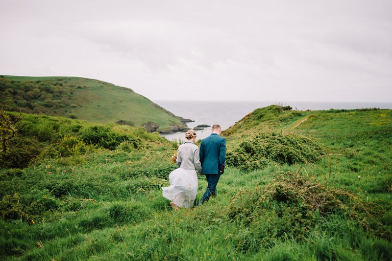 Bride and groom walking on hill by sea