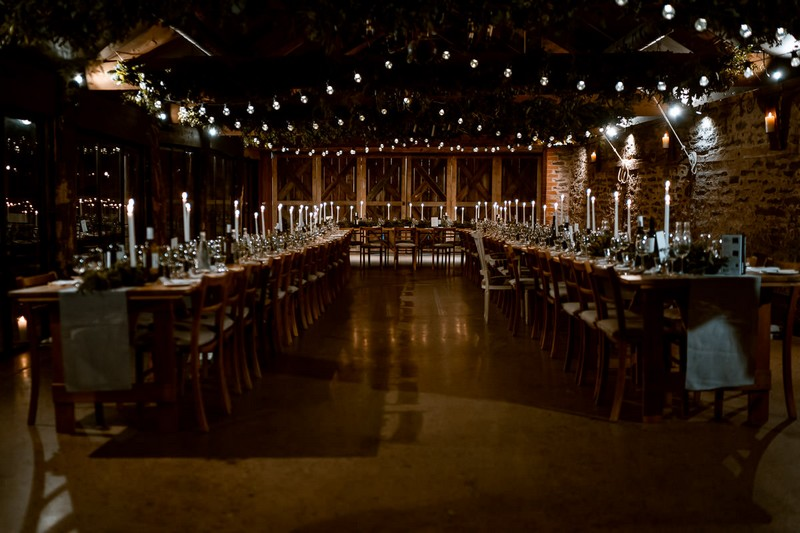 Long rustic wedding tables in The Wainhouse at Dewsall Court