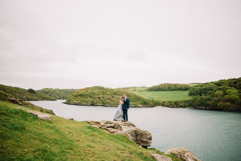 Bride and groom on rock by sea