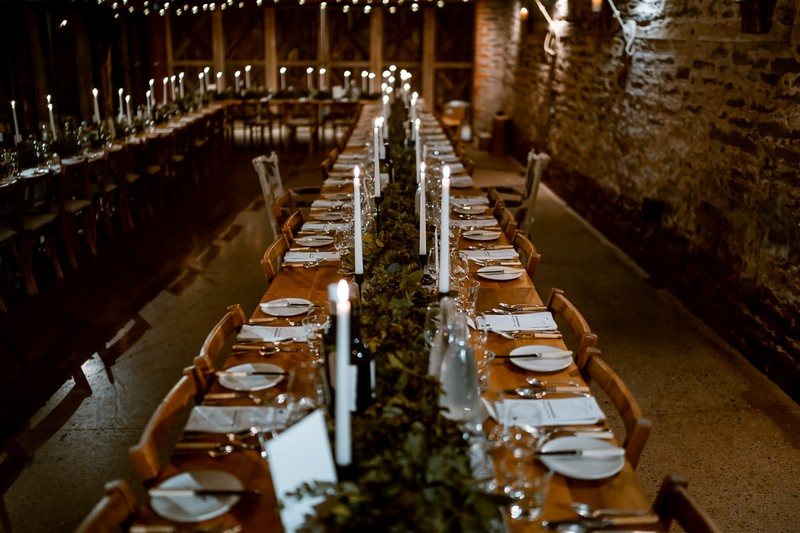Long wedding table with rustic styling in The Wainhouse at Dewsall Court