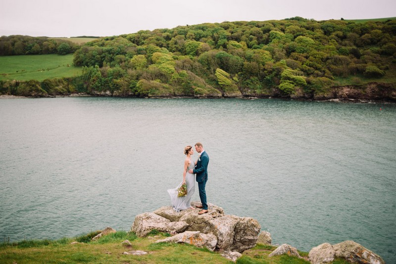 Bride and groom standing on rock by Devon coastline