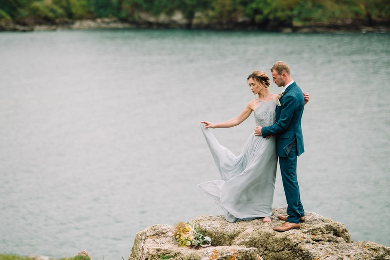 Bride holding out dress as she stands on rock with groom