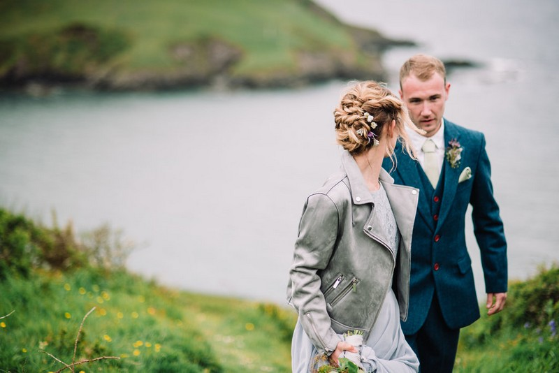 Bride in grey leather jacket walking with groom