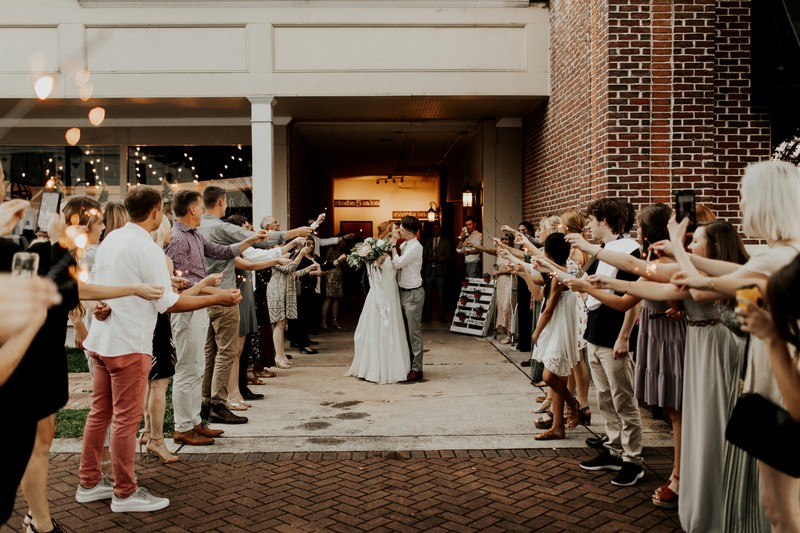 Bride and groom kissing in middle of guests with sparklers