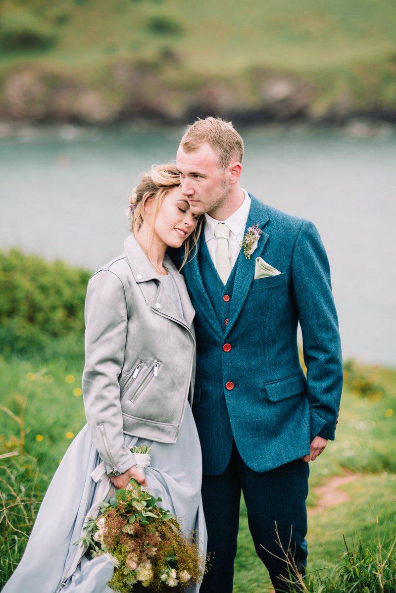 Bride in grey leather jacket resting head on groom