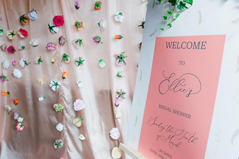 Hanging flower backdrop next to bridal shower welcome sign