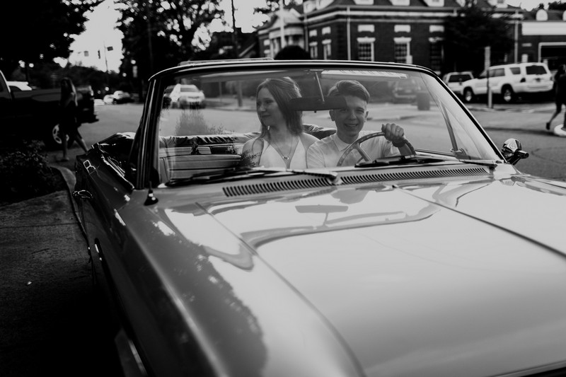 Bride and groom sitting in 1964 convertible Rambler
