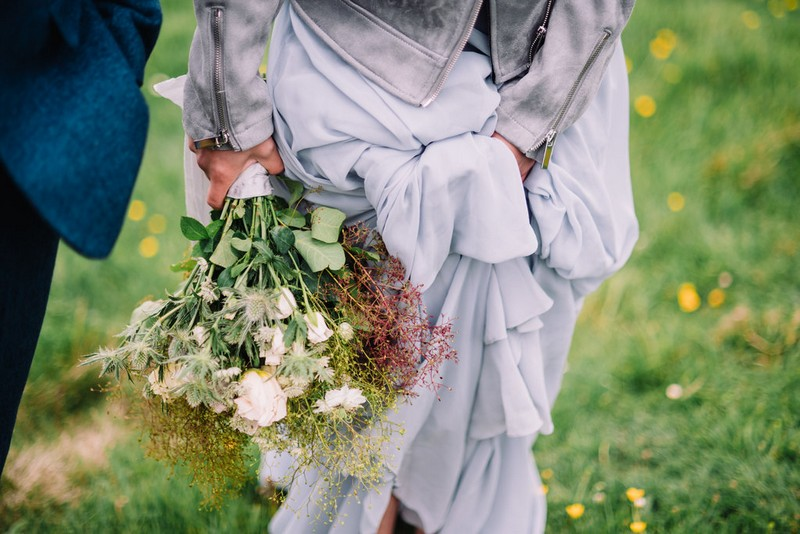 Bride's wild bouquet and bottom of her grey dress