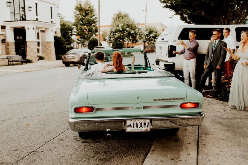 Bride and groom leaving wedding in 1964 convertible Rambler