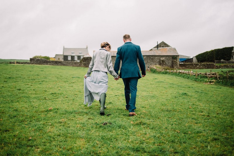 Bride and groom holding hands as they walk across farmland to wedding venue