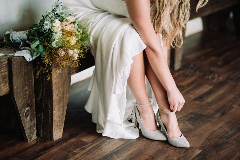 Bride putting on grey shoes