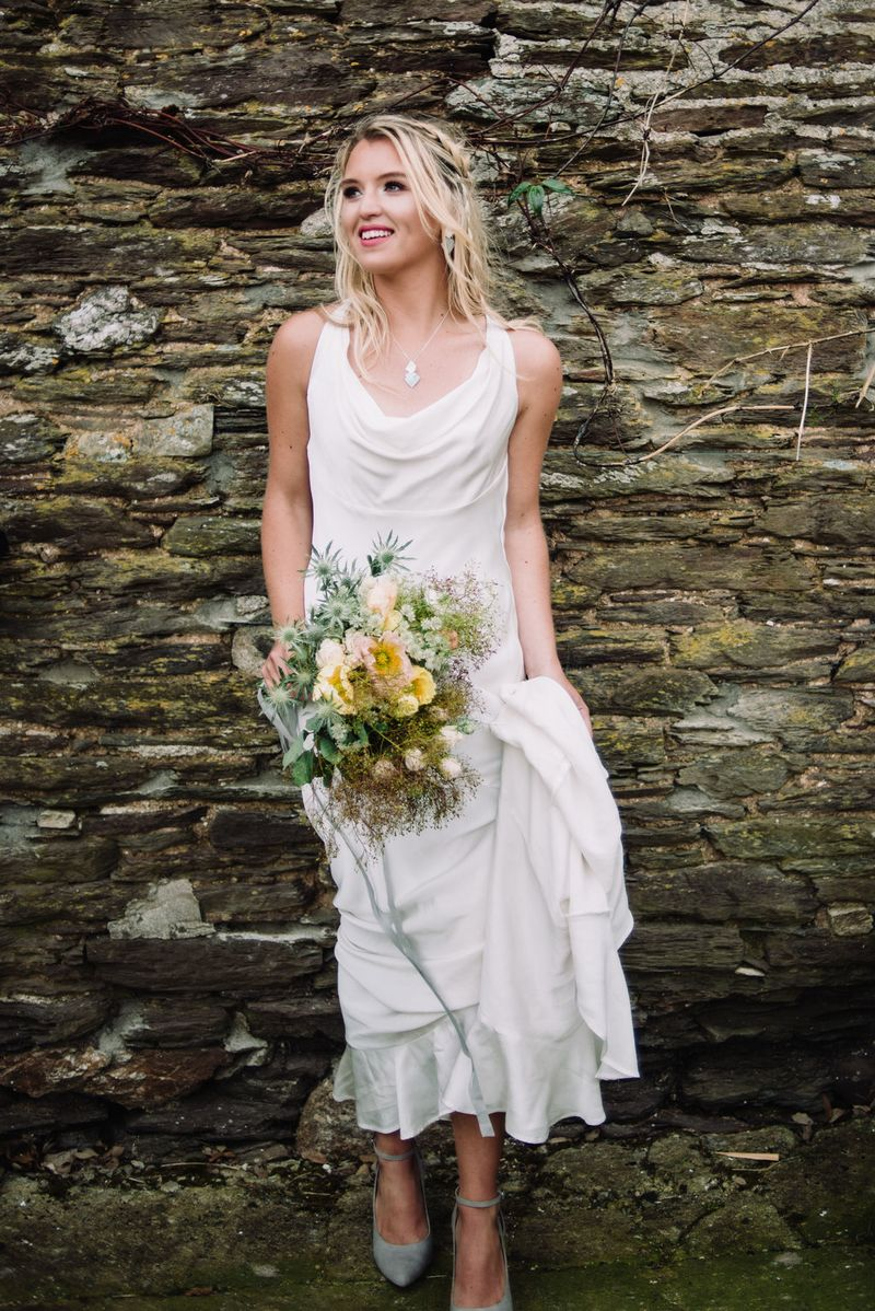 Bride holding bouquet as she stands against wall