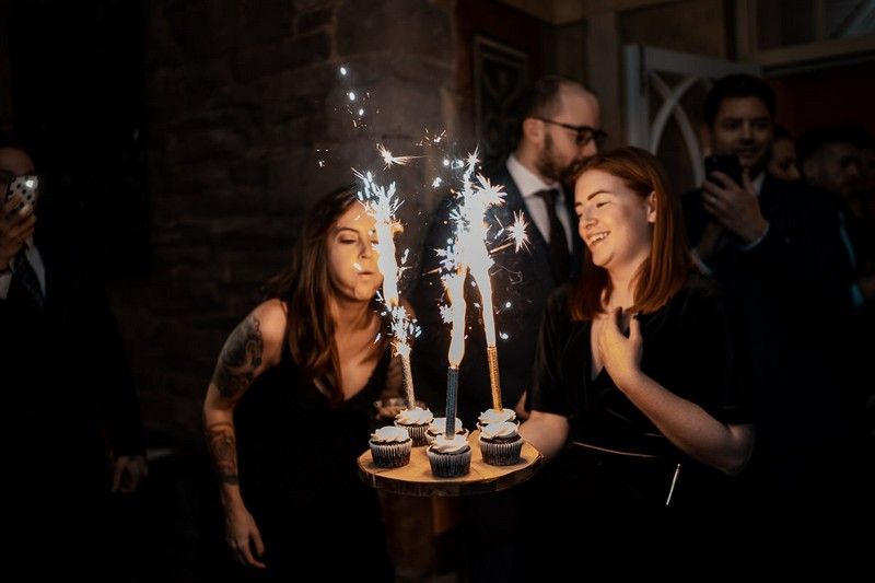 Woman blowing sparklers on cupcakes