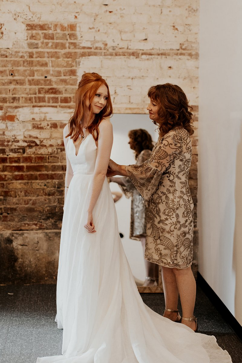 Bride's mother helping bride do up wedding dress
