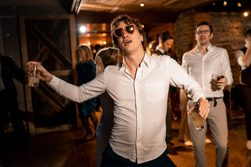 Wedding guest dancing with heart sunglasses on