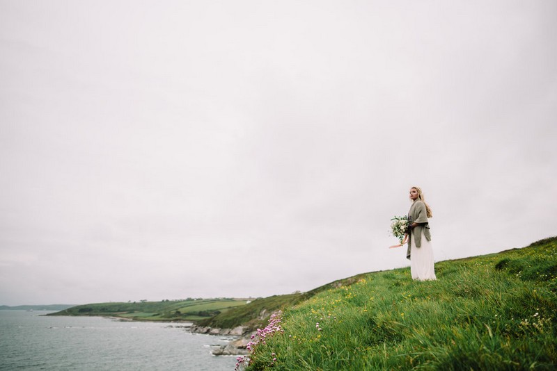 Bride standing looking out at coastline