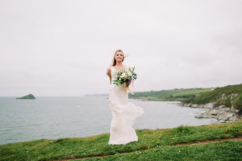 Bride standing by Devon coastline