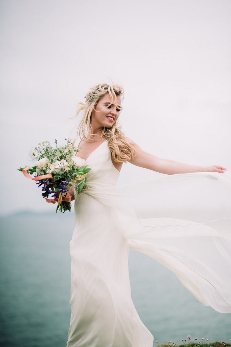 Bride holding out dress as it blows in the wind