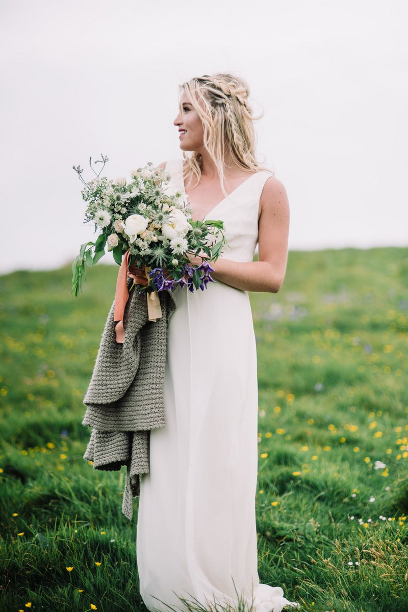 Bride holding bouquet and shawl
