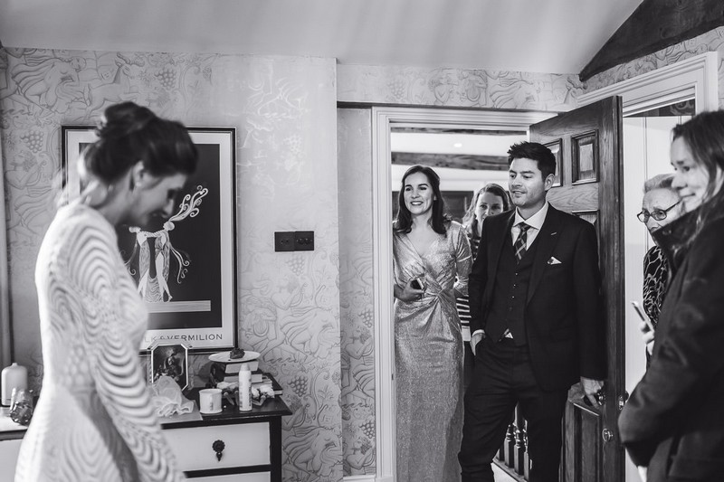 Man and bridesmaids seeing bride in wedding dress before wedding