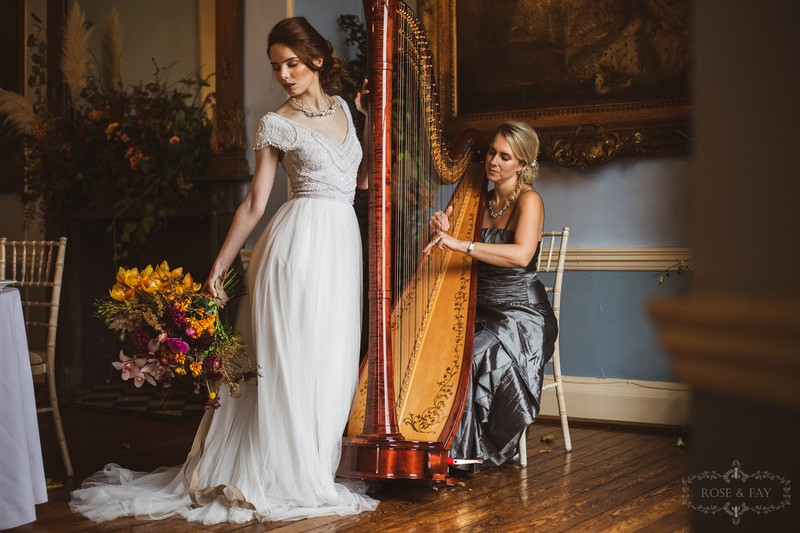 Elegant bride standing next to wedding harpist
